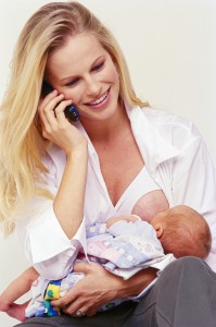 view of a woman breast feeding and talking on a mobile phone