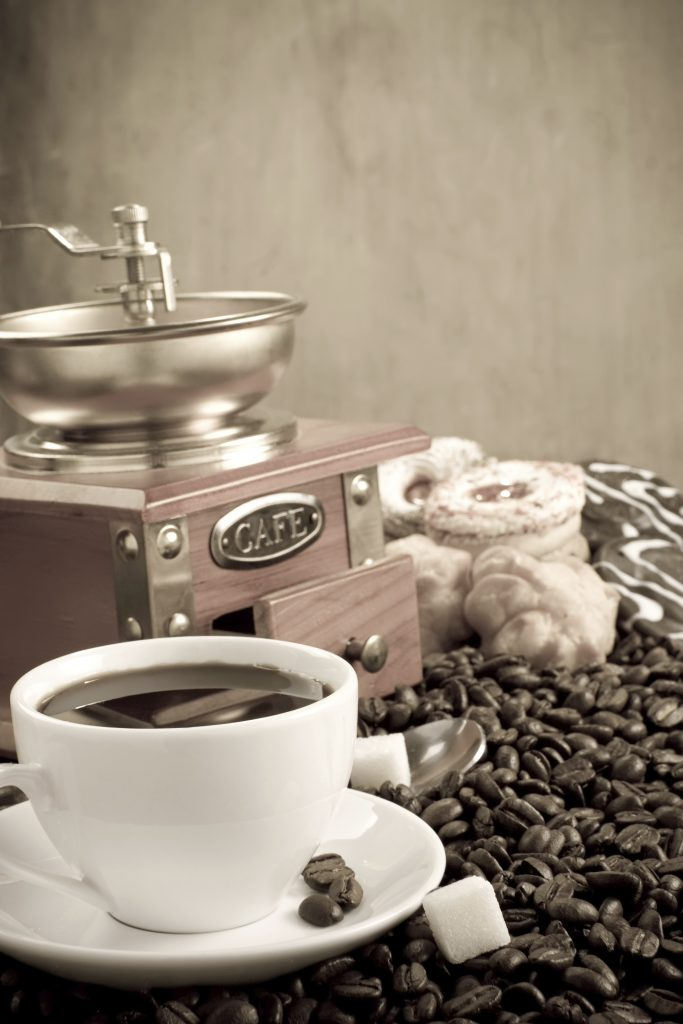 cup of coffee, beans, pot and grinder on wood